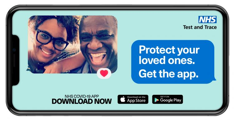 Image of a smartphone screen. the left corner has a selfie of an older man with a younger woman, both smiling at the camera. The upper right corner has the NHS test and trace logo and a speech bubble