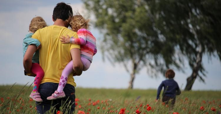A man holding two young children walking in a poppy field along with another young girl