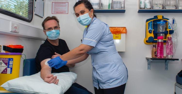 man getting a blood test at a mobile clinic