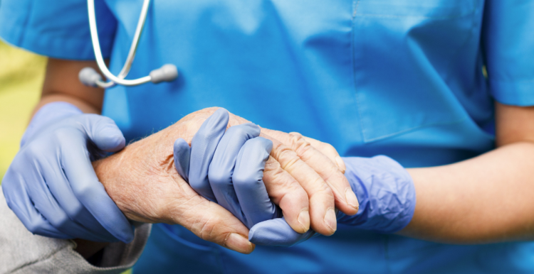 A healthcare worker holding the hand of an elderly person while wearing protective gloves