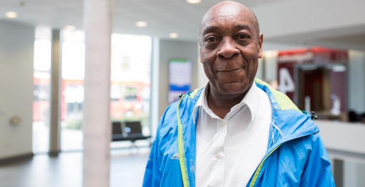 Older black man standing at a hospital ward