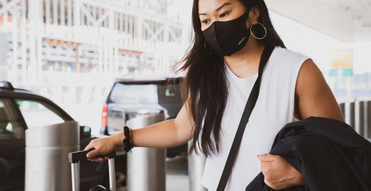 Young Asian woman wearing a face mask and holding carry on luggage outside an airport