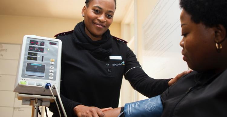 A black woman getting her blood pressure tested by a black female clinician