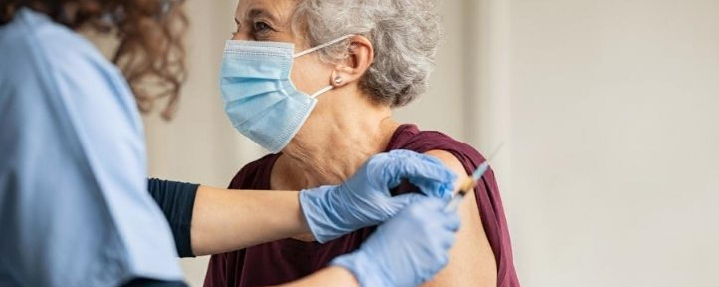Female health worker vaccinating an elderly woman