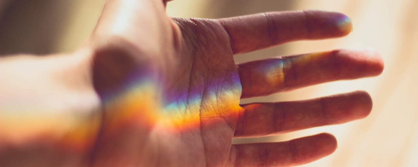 A hand gently spread out with a colourful light reflection going across it
