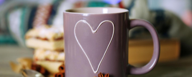 a mug with a hear shape on it on a cosy autumn background