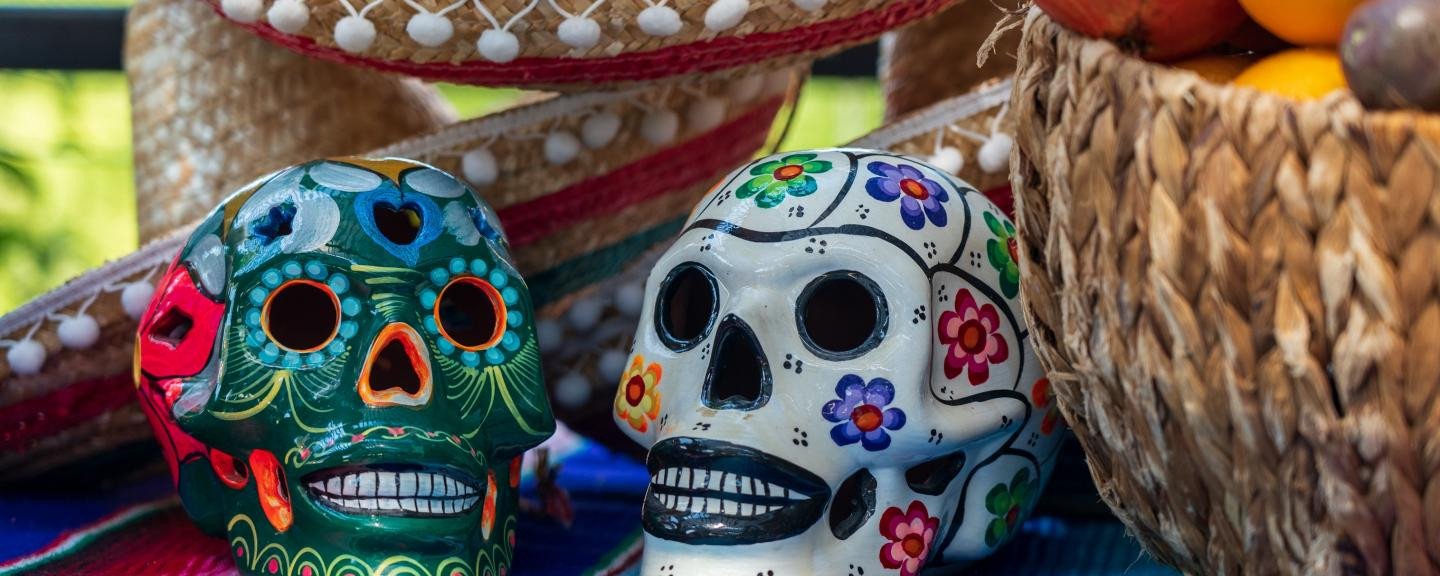 A colourful arrangement of decorative sculls, baskets and hats to celebrate the mexican Day of the Dead