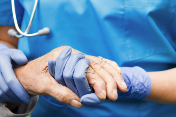 Nurse holding the hand of elderly person