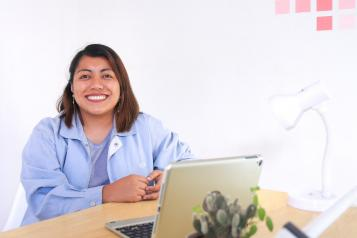 Lady in the blue jacket smiling in front of a laptop