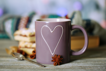 a mug with a hear shape on it on a cosy autumn background