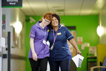 Two female nurses hugging at a hospital ward