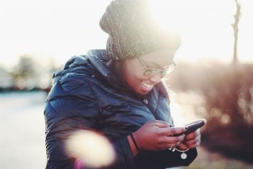 A smiling black woman looking at her smartphone standing at a park