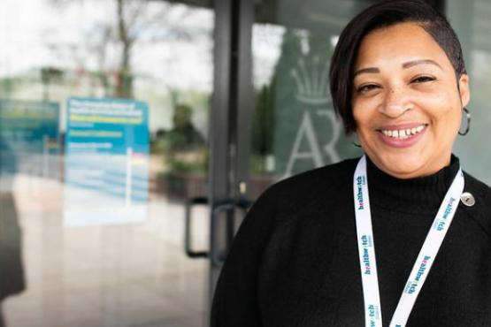 A smiling woman standing in front of the entrance to a health service