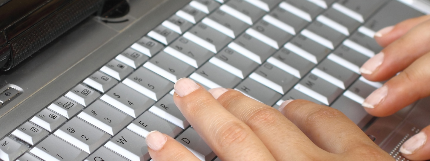 Close up of hands typing on a laptop keyboard