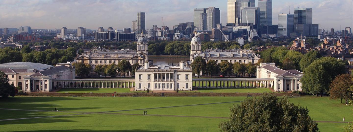 A photo of Greenwich park on a sunny day, taken from a hilltop facing the Royal Naval College and Canary Wharf