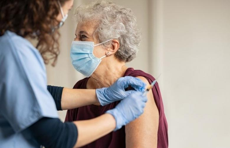 Older female person getting the COVID-19 vaccination from female health worker