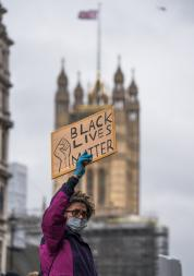 "a protester holding up a ""black lives matter"" sign with the houses of parliament in the background"