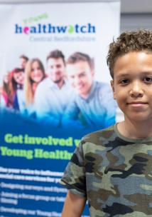 Young male volunteer standing in front of Healthwatch branding