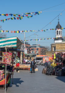 A man walking through colourful Woolwich market on a sunny day